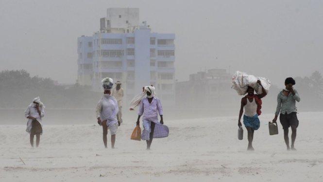 Người dân Ấn Độ băng qua bờ sông Ganga ngày 3-5-2019 giữa ảnh hưởng của bão Fani. Ảnh: IANS