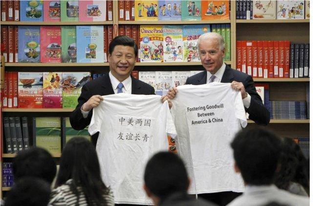 """Ông Tập (trái) chụp ảnh với ông Biden trong chuyến thăm Mỹ năm 2012. Dòng chữ trên chiếc áo ông Tập cầm: """"Trung Mỹ lưỡng quốc, hữu nghị trường thanh"""" - """"Tình hữu nghị hai nước Trung - Mỹ mãi mãi xanh tươi"""". Ảnh: AP"""
