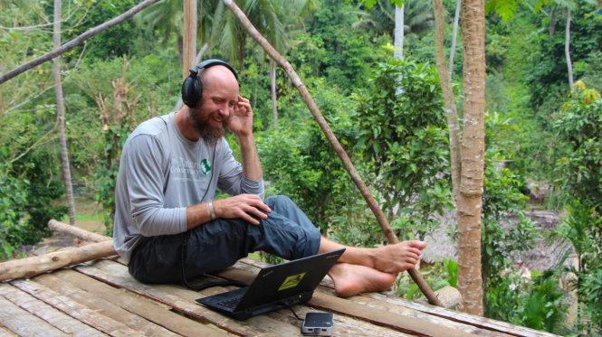 Eddie Game lắng nghe dữ liệu âm thanh ghi nhận trong rừng. Ảnh: The Nature Conservancy
