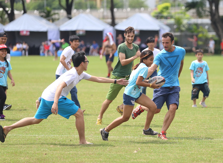 Các cô cậu nhóc VN vui vẻ tập luyện bóng bầu dục với người nước ngoài. Ảnh: H.Đ