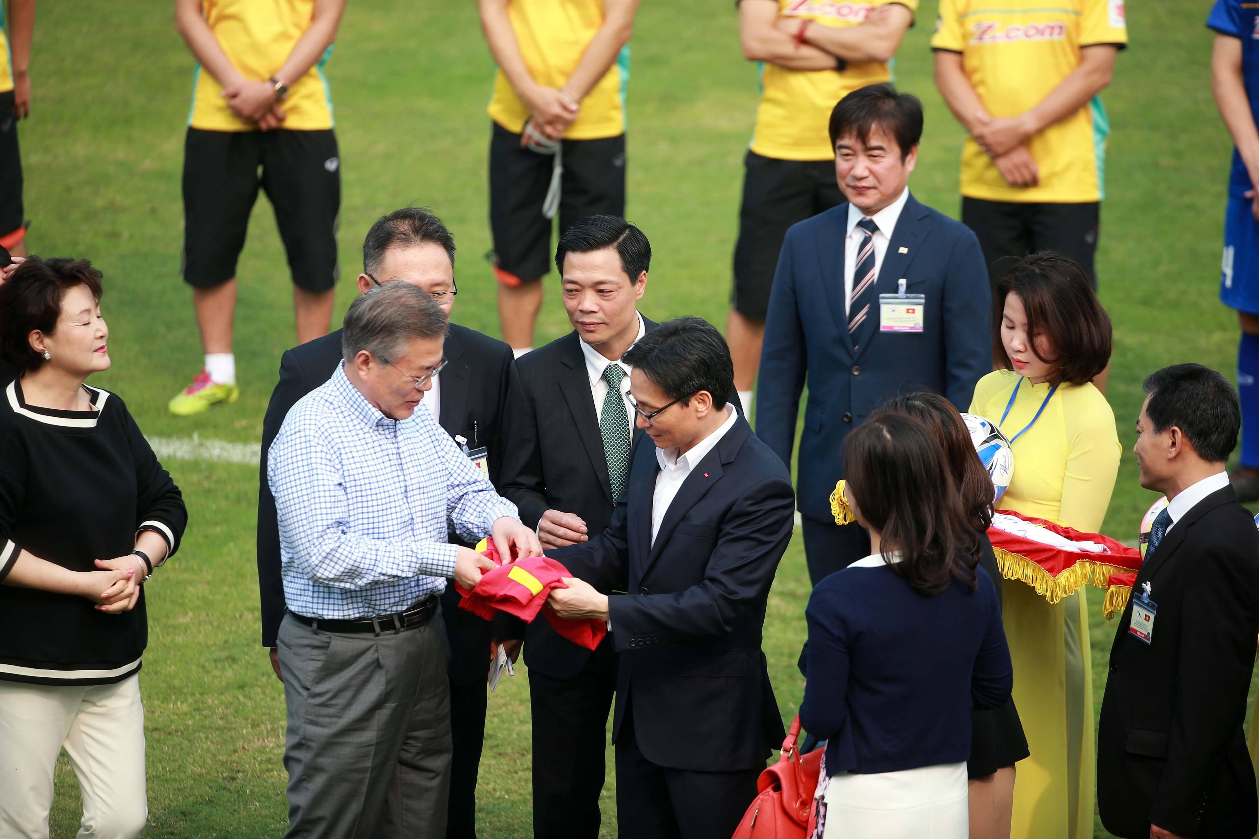 Phó Thủ tướng Vũ Đức Đam trao áo khoác cho Tổng Thống Hàn Quốc trước khi hai ông tham gia đá bóng cùng HLV Park Hang Seo và Xuân Trường. Ảnh: NAM KHÁNH