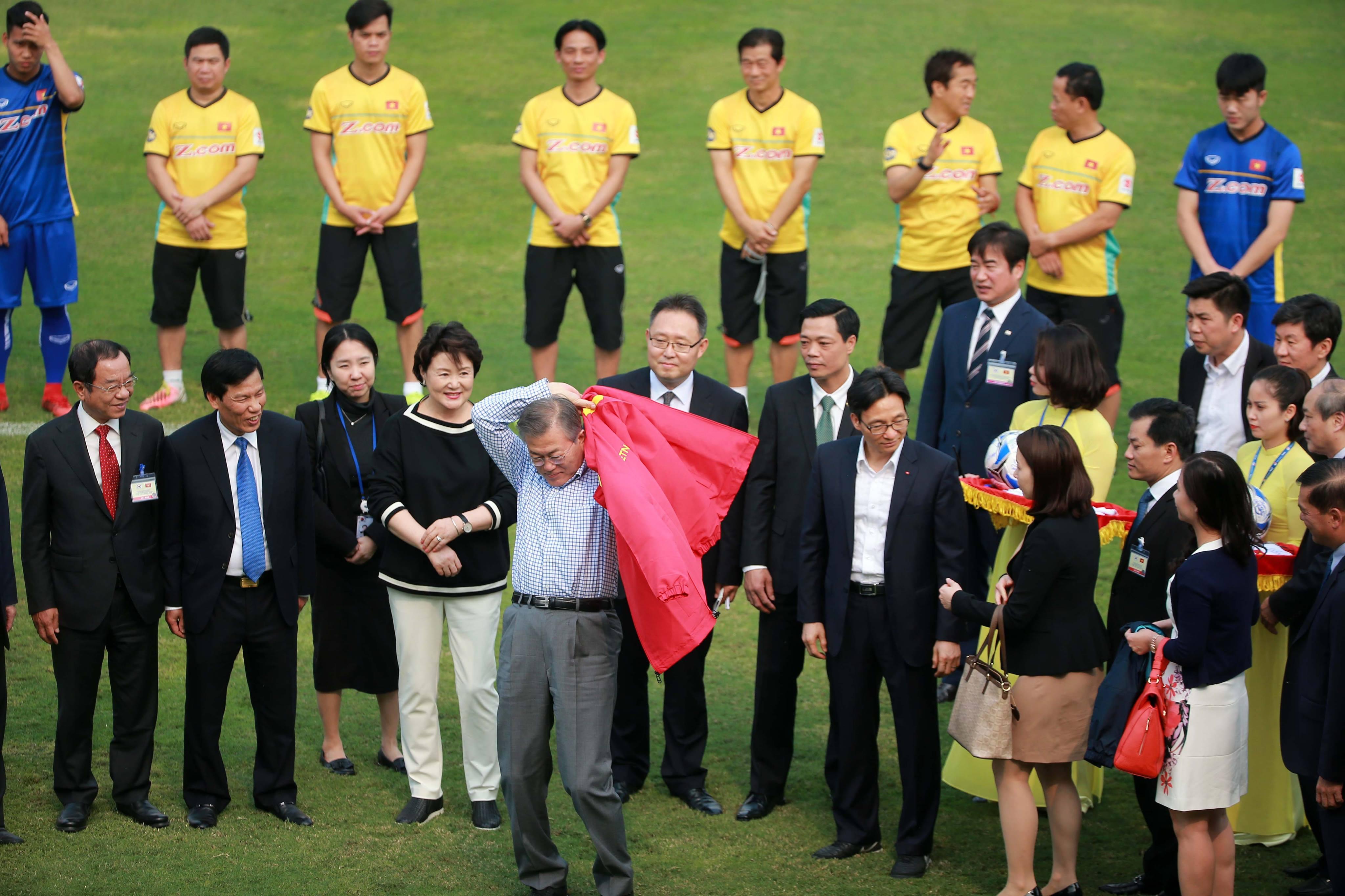 Tổng thống Hàn Quốc khoác áo của đội tuyển VN vào người trước khi cùng đá bóng với phó Thủ tướng Vũ Đức Đam. Ảnh: NAM KHÁNH