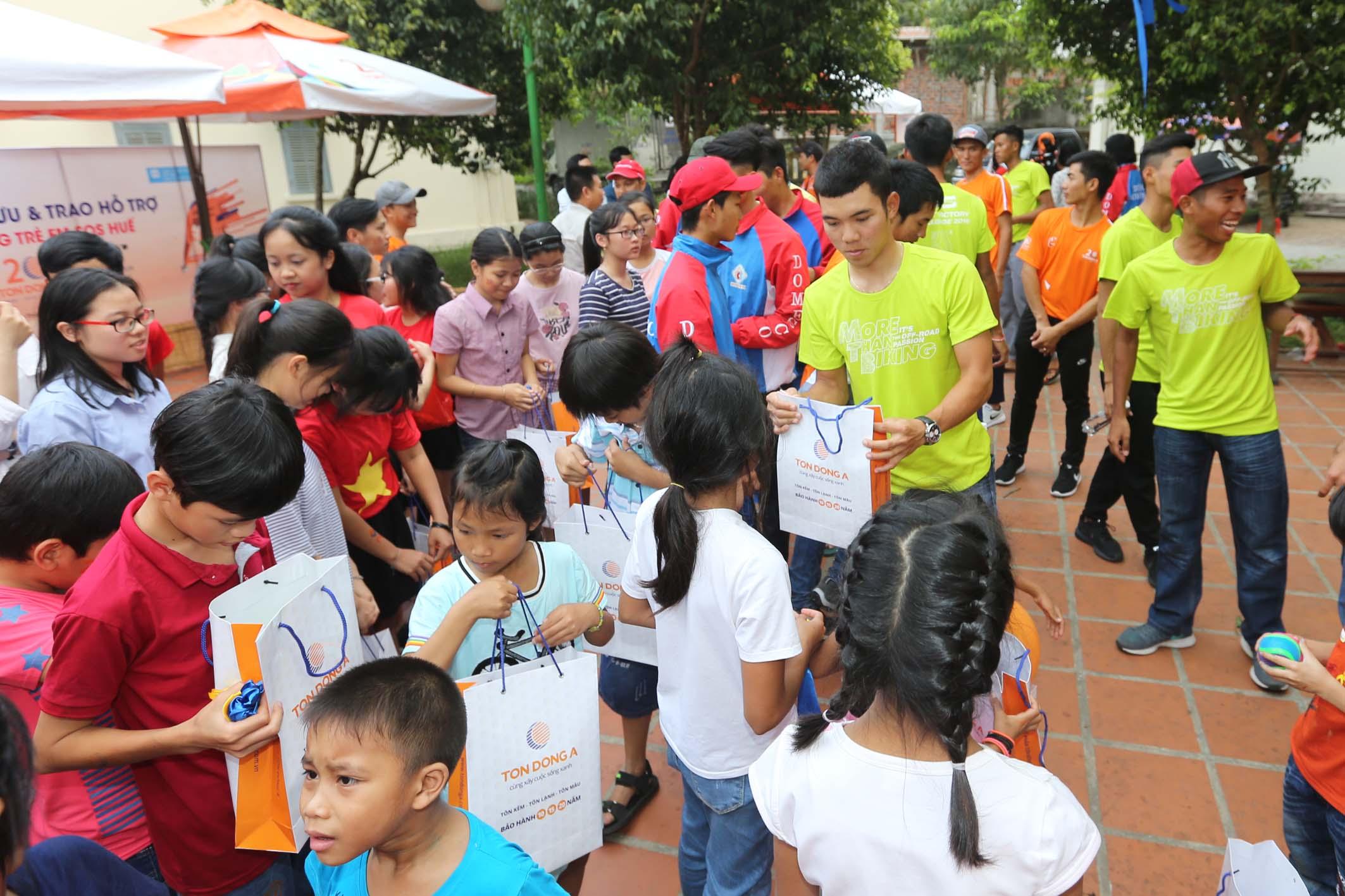 Các tay đua tặng quà cho trẻ em làng SOS Huế  Ảnh: M.Q.