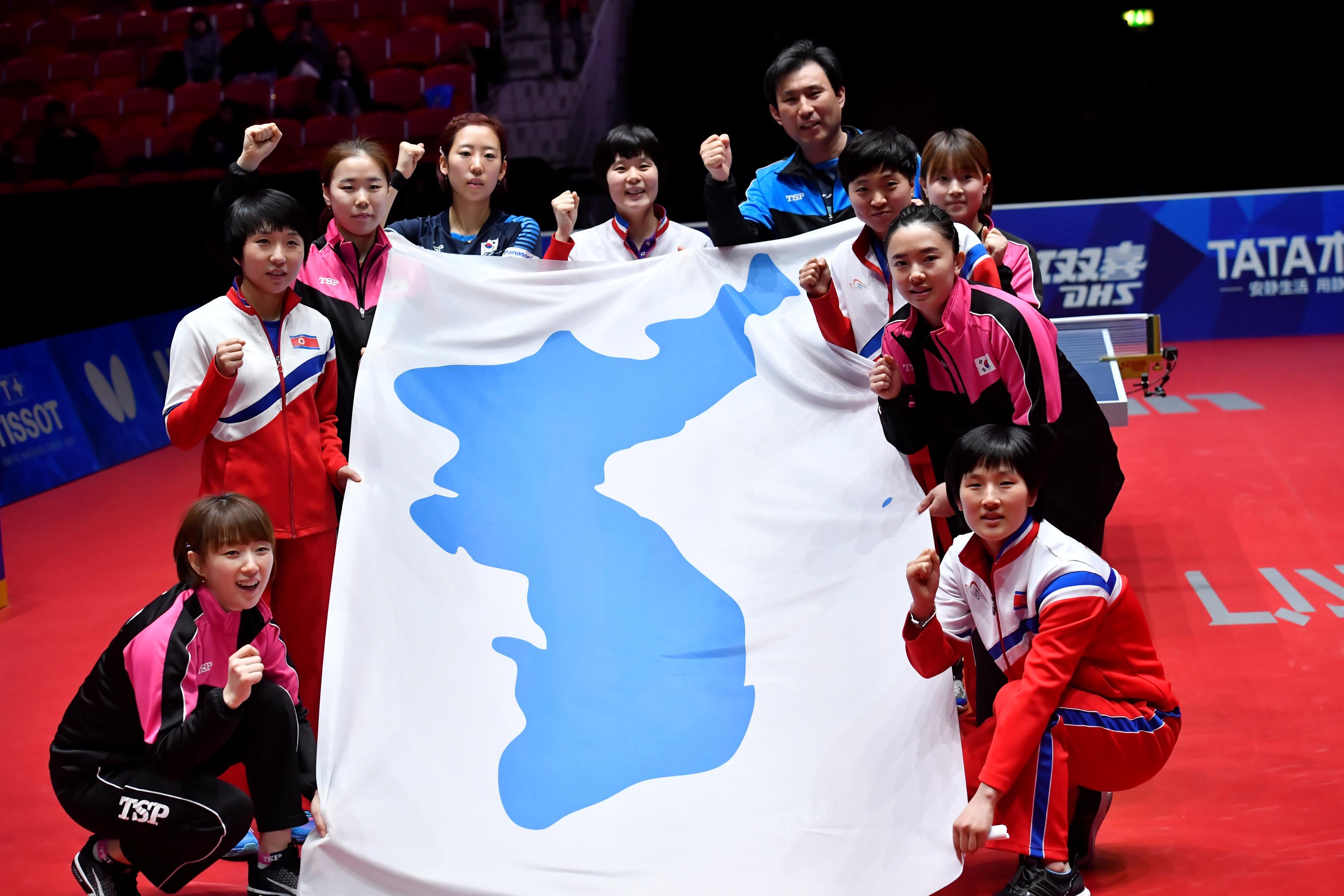 Các thành viên tuyển bóng bàn nữ Hàn Quốc - Triều Tiên thống nhất vui vẻ bên lá cờ đặc biệt. Ảnh: REUTERS
